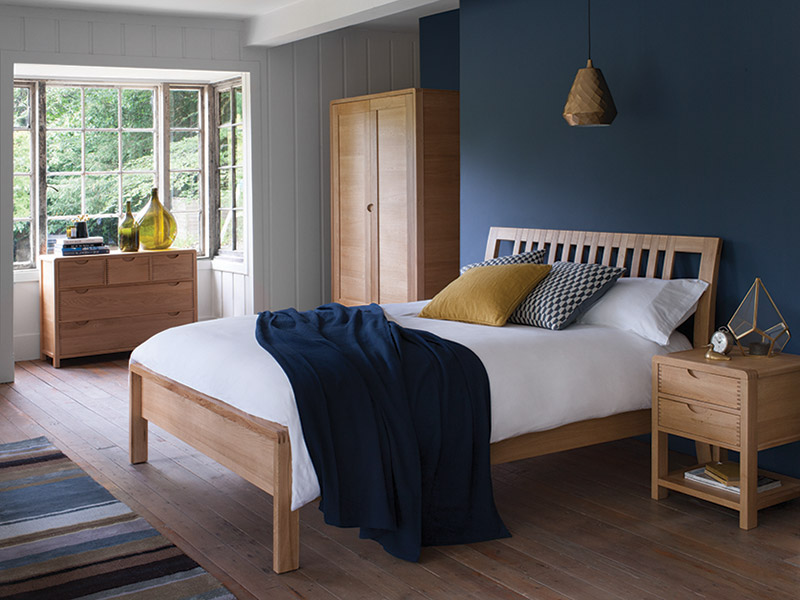 Bosco bedroom furniture with blue blanket on bed and blue walls behind